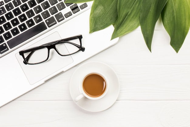Black eyeglasses and leaves on an open laptop with coffee cup on wooden desk