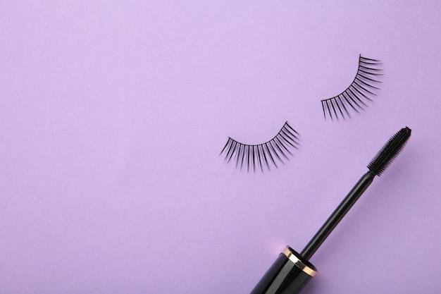Черные ресницы и тушь на фиолетовом фоне. вид сверху. концепция красоты