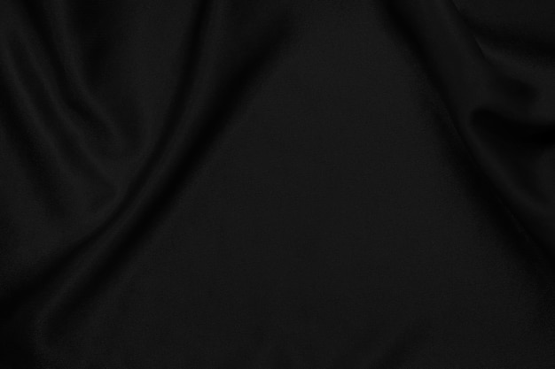 Black fabric texture background, crumpled pattern of silk or linen.