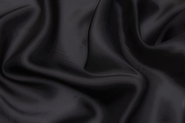 黒の生地の質感の背景、波状の生地の滑りやすい黒い色、豪華なサテンまたはシルクまたはウールの布の質感。