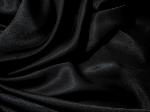 黒い生地の質感、波状の生地の滑りやすい黒い色、豪華なサテンの布の質感。