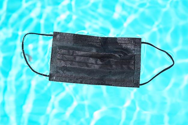 수영장 물에서 코로나 바이러스(covid-19)로부터 보호하기 위한 검은색 얼굴 마스크.