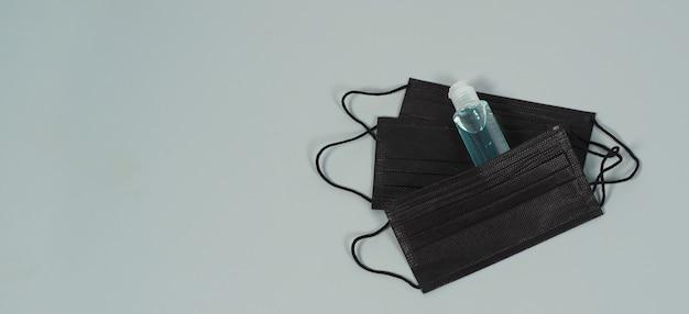 灰色の背景に黒いフェイスマスクとアルコールジェル。 covid-19、インフルエンザおよびその他の空中感染に対する保護。コピースペース