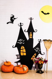 Black fairy castle, witch on the white wall and decorative pumpkins. decor for he celebration of halloween