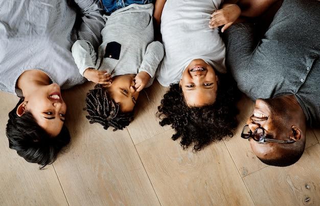 Черная семья, лежащая на деревянном пространстве