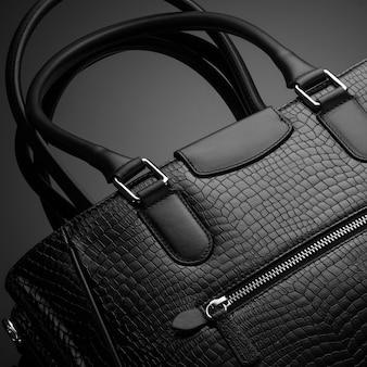 Черная модная дизайнерская женская сумка на темном фоне