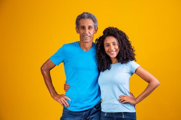 笑顔のカメラを見ている黒人の父と娘