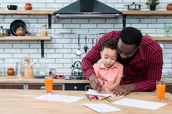 Черный отец и сын рисуют за столом