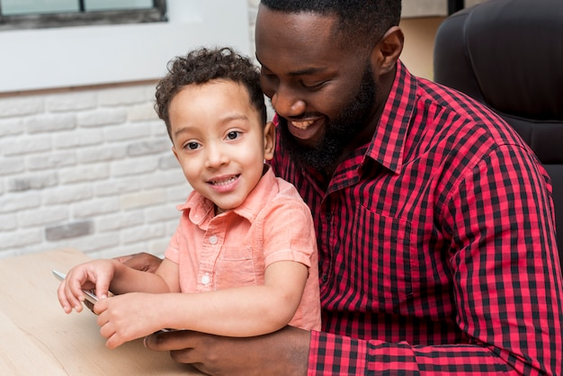 Black father and cute son using tablet