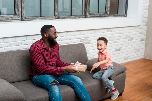 Black father giving gift box to amazed son