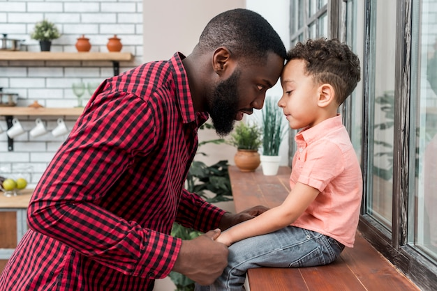 Black father holding hand of son on window sill