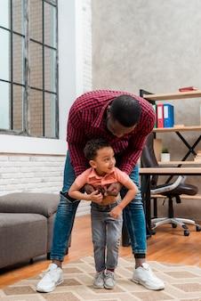 Black father hugging little son