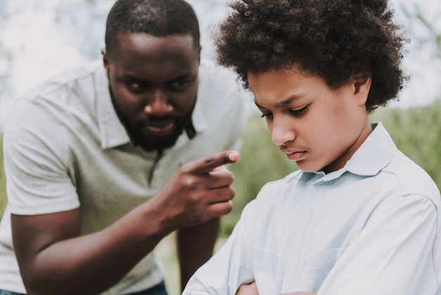 Black father scolds son and boy turned away from him