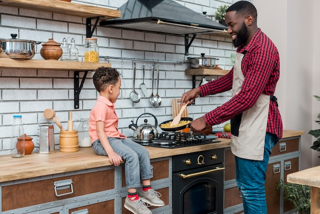 Black father and son cooking in kitchen