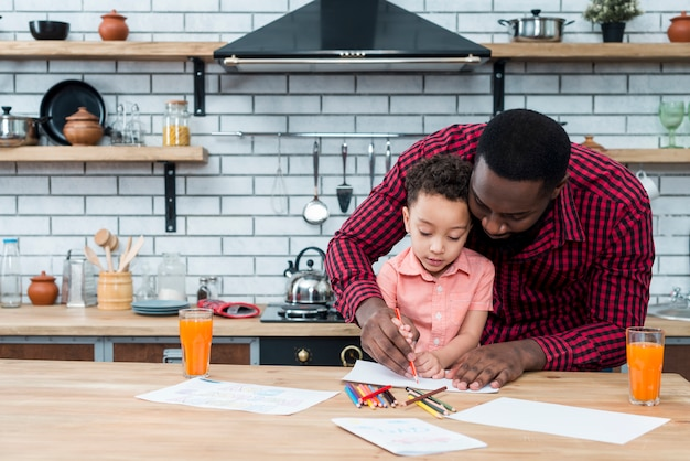 Black father and son drawing at table