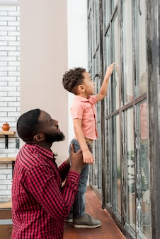 Black father and son looking at window pointing away