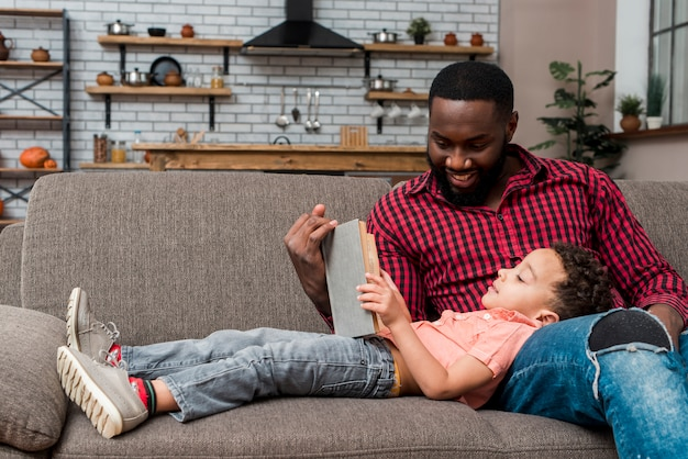 Black father and son reading book on couch