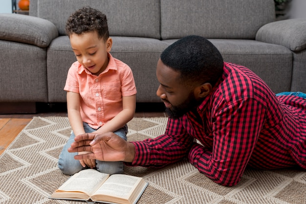 Black father and son reading book on floor
