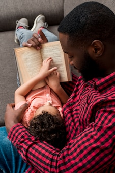 Black father and son reading book on sofa