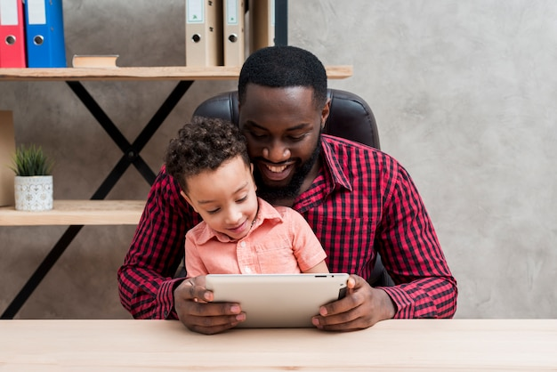 Black father and son using tablet at table