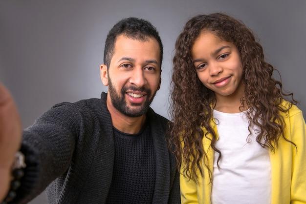 黒人の父親が娘と一緒にセルフィーを撮る
