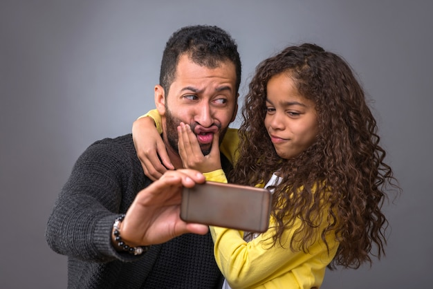 Black father taking selfies with his daughter