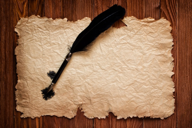 Black feather and old paper on the background of a brown table