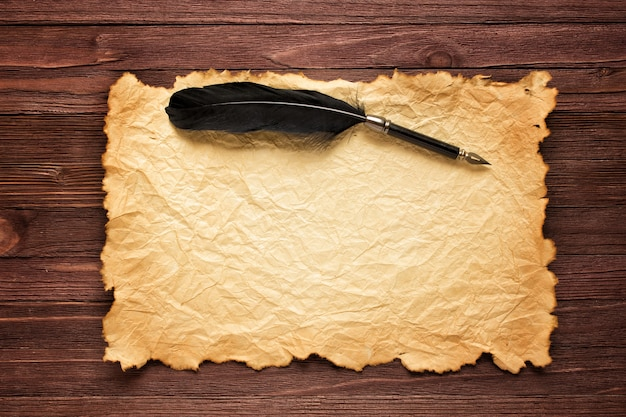 Black feather and old paper on the of a brown table