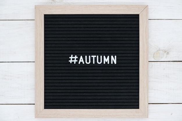 Черная фетровая доска с хэштегом и словом осень на английском языке на белом деревянном столе