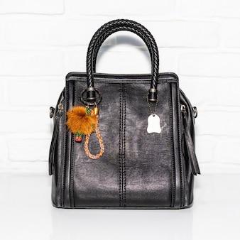 白い表面に黒い女性のバッグ