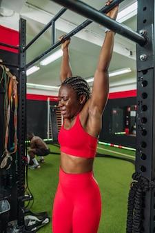 스포츠 체육관에 있는 흑인 여성 보디빌더는 등 바벨 운동을 한 후 매우 피곤합니다. 체육관에서 몸을 강화하는 개념