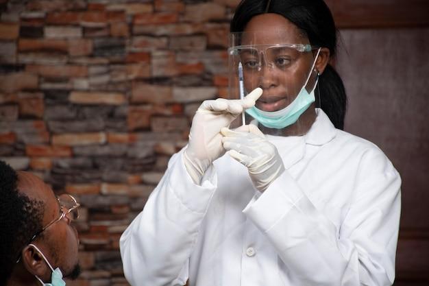彼女が患者に投与しようとしている投与量に注意している黒人女性医師