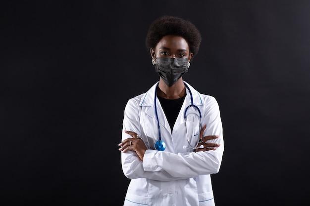 Черная женщина-врач в маске на черном фоне. афро-американская женщина в медицинском халате со стетоскопом стоя и улыбается.