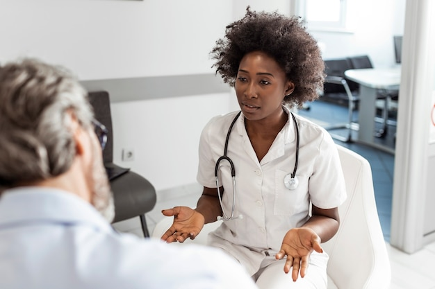 Black female doctor and senior man communicating in a waiting room at hospital.