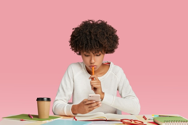 Black female manager looks seriously at smart phone, wears white sweater, keeps pen in hand