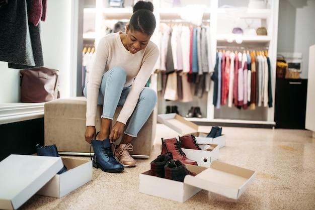 신발에 노력하는 흑인 여성 사람. 의류 매장, 소비 라이프 스타일, 패션의 쇼핑 중독