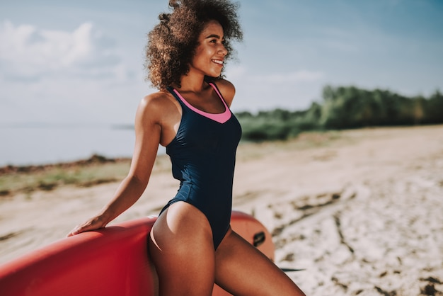 Black female in swimsuit lean on surf at beach