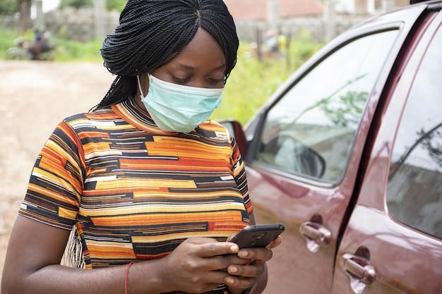 フェイスマスクを身に着けて、屋外で彼女の電話を使用している黒人女性-新しい通常の概念