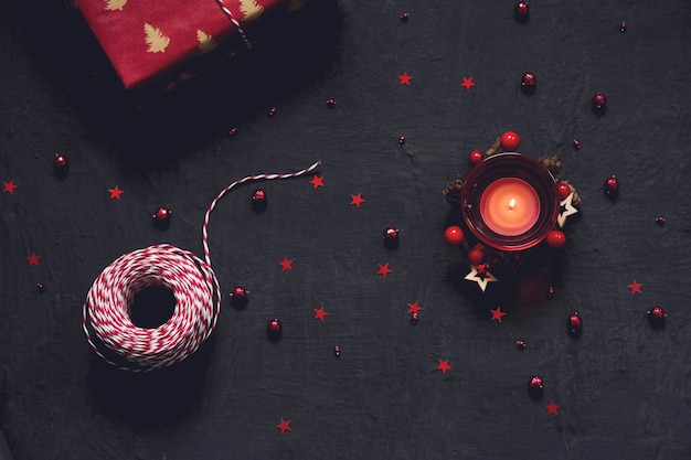 Black festive background with red decoration, candle and gift, chrtistmas and new year greeting card with place for text