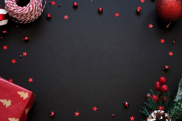 Black festive background with red decoration. christmas greeting card with place for text