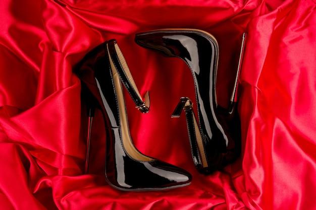 赤いサテンにアンクルストラップが付いた黒のフェチ光沢のあるパテントレザーのスティレットハイヒール