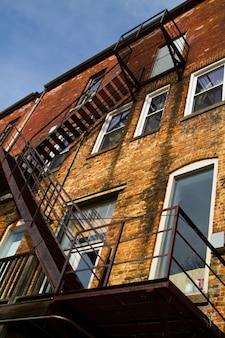 Черные ступеньки пожарной лестницы поднимаются на кирпичное здание с множеством окон