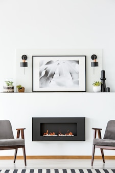 Черный камин между серыми креслами в белом плоском интерьере с плакатом между лампами. реальное фото