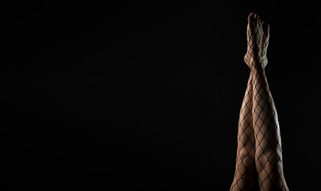 Черные колготки в сеточку на тонких ногах, поднятые над черным фоном баннера с местом для текста