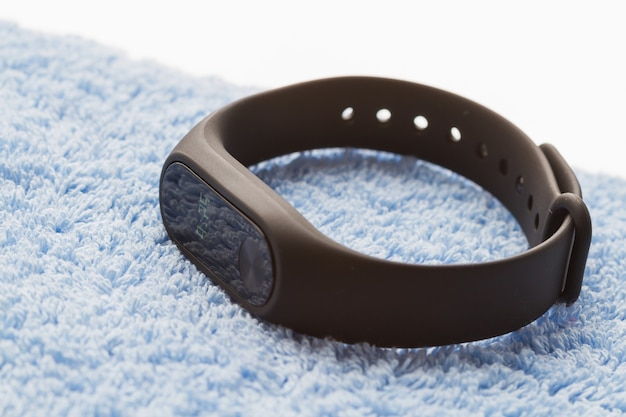 Black fitness watch on the blue textile surface