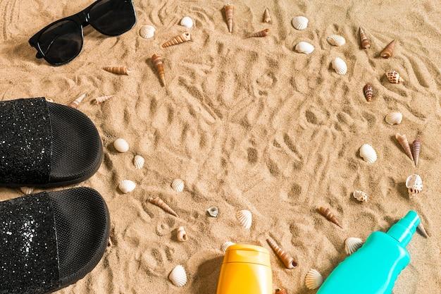 黒のビーチサンダルとサングラス、砂の上の貝殻。あなたのテキストのための場所で。上面図