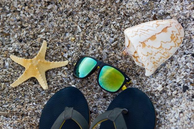 太陽が降り注ぐビーチで、黒いビーチサンダル、素敵なヒトデと大きな貝殻のカラーサングラス。上面図。夏のコンセプト。