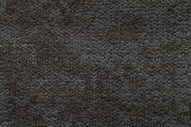 Black fluffy background of soft, fleecy cloth, texture of light nappy textile,