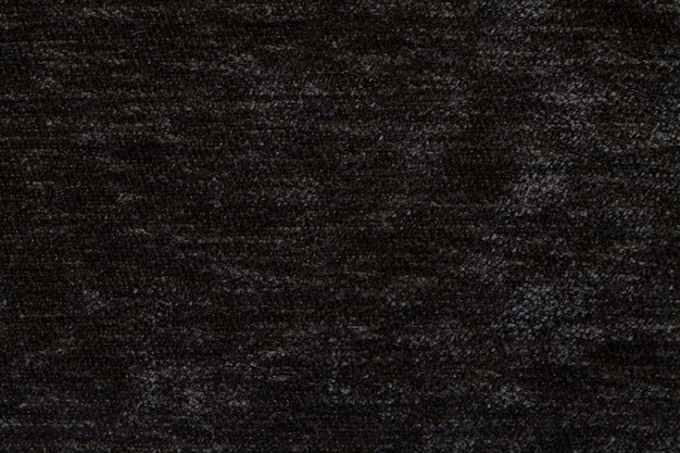 Black fluffy background of soft, fleecy cloth. texture of textile closeup.