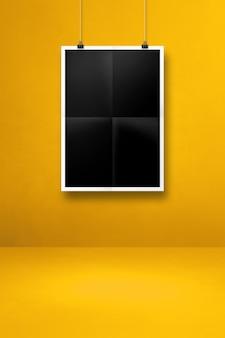 클립이 있는 노란색 벽에 검은색 접힌 포스터가 걸려 있습니다. 빈 모형 템플릿